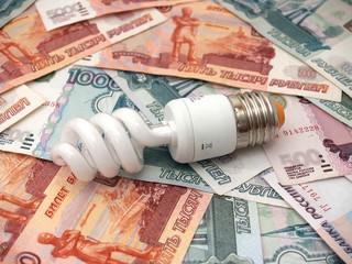 Энергосберегающая лампочка лежит на бумажных российских деньгах