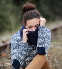 Retrato de mujer joven semitapada con bufanda de lana