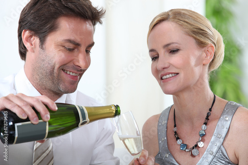 Man serving cup to blonde woman