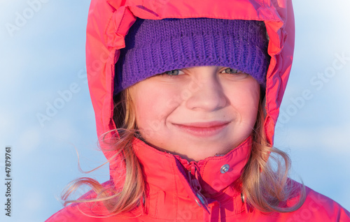 little ruddy nice girl in winter outwear with hood smiles