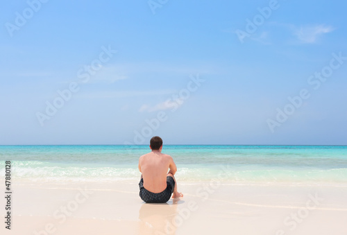 Young man sitting alone on a tropical beach