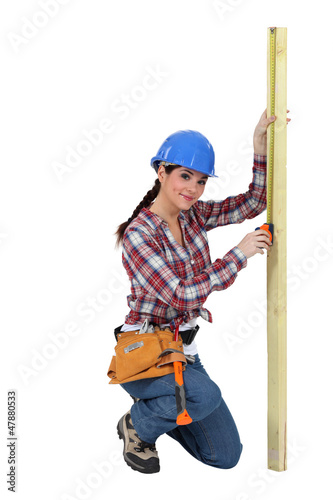 Woman measuring a piece of wood