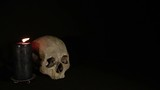 Skull and candle on the black background