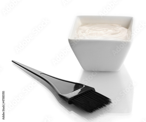 Bowl with hair dye and black brush for hair coloring, isolated