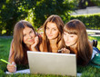 Happy young student girls using a laptop outdoors