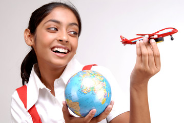 Indian girl holding globe and a toy aircraft