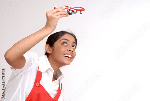 Portrait of girl holding toy aircraft