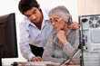 Young man showing elderly lady how to use computer
