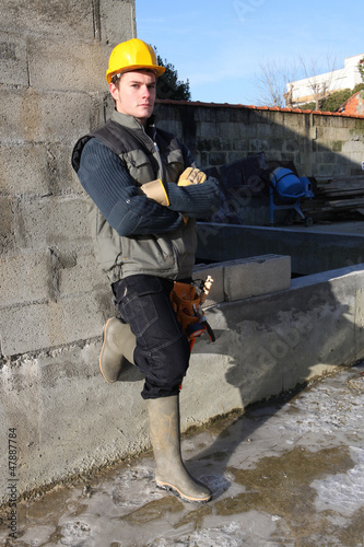 Builder casually leaning against wall