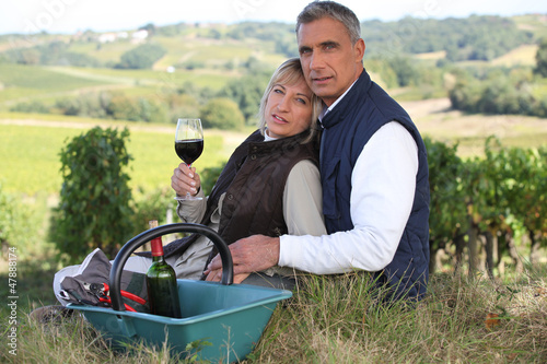 Couple drinking wine by vineyard