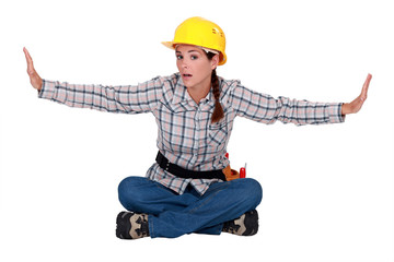 Female builder sitting with arms stretched