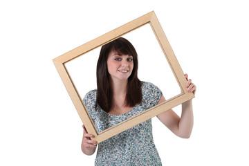 Brunette holding empty frame