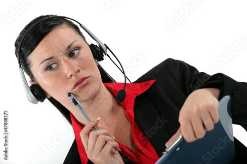 receptionist with headset and side look taking a call