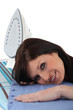 Woman laying her head on an ironing board