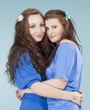 two young female friends hugging, looking