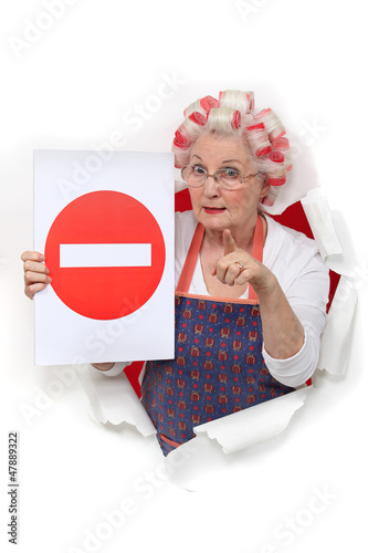 Elderly lady with hair rollers issuing warning