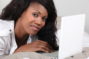 Afro-American woman laid in front of laptop