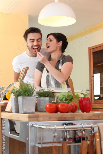 a woman feeding a carrot to her husband
