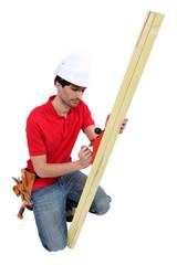 A carpenter using a plane.