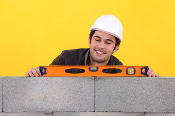 Up-beat mason using spirit-level on wall