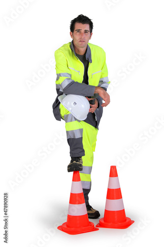 Traffic worker stood with cones