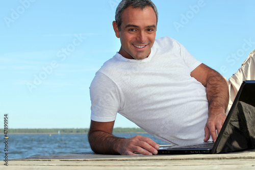 Man looking his laptop by the lake