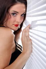 Woman spying through venetian blinds