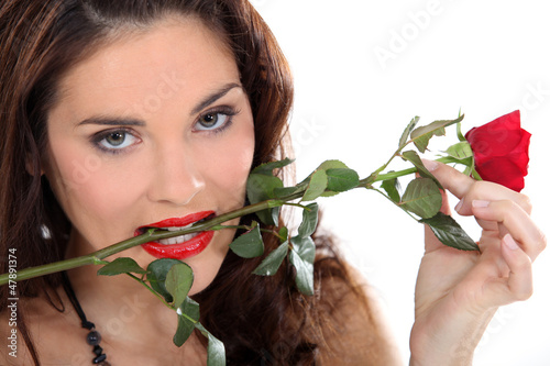 Woman with a red rose in her teeth