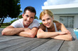 Young couple relaxing on pool deck after exercising