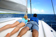 Couple relaxing on a sailing boat while cruising