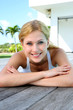 Smiling woman laying on pool deck after exercising