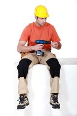 Man sat holding cordless drill