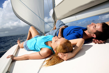 Young couple relaxing on sailboat deck
