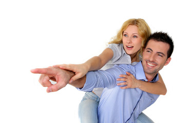 Cheerful couple pointing at one side