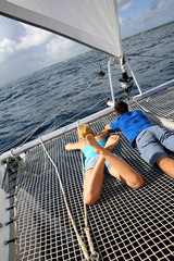 Couple relaxing on catamaran net looking at the sea