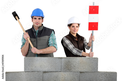 craftsman and craftswoman standing behind a stone block wall