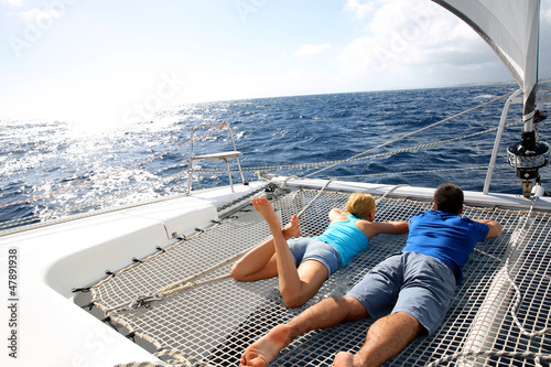 Papiers peints Voile Couple relaxing on catamaran net looking at the sea