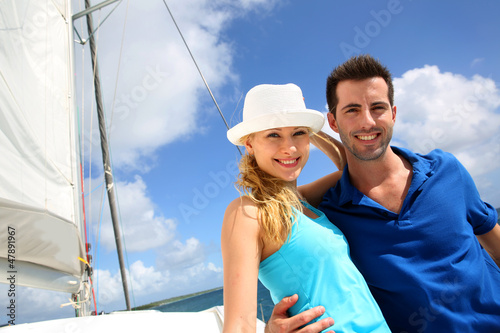 Smiling rich young couple on a sailboat in Caribbean sea