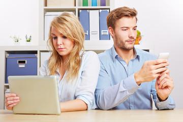 Paar mit Smartphone und Tablet PC