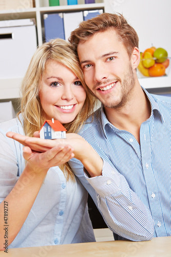 Lachendes Paar trägt kleines Haus