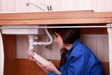 Young female apprentice plumbing a sink