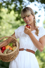 Blond woman carrying fruit basket