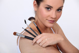 beautiful woman holding make up brushes