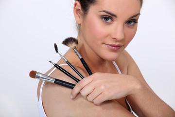 beautiful woman holding make up brushes