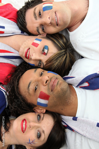 Four French football supporter laying together
