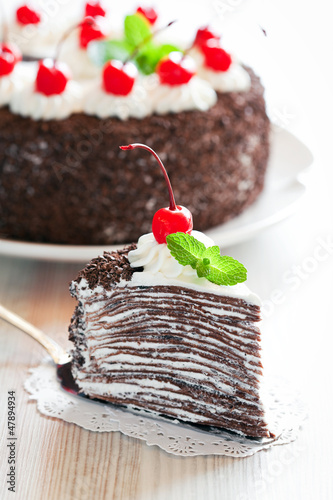 Piece of chocolate crepe cake with whipped cream and cherries