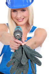 Tradeswoman aiming a screwdriver