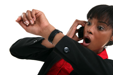 businesswoman consulting her watch open-mouthed