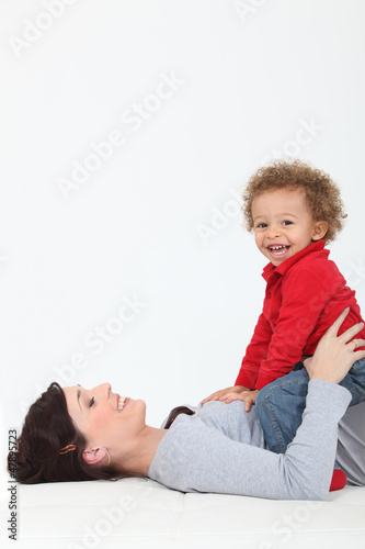 Mother resting son on belly