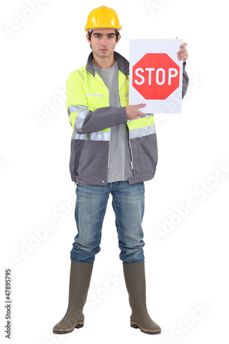 bricklayer holding stop sign